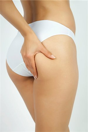 Woman pinching body fat on buttocks, cropped Stock Photo - Premium Royalty-Free, Code: 632-05816887