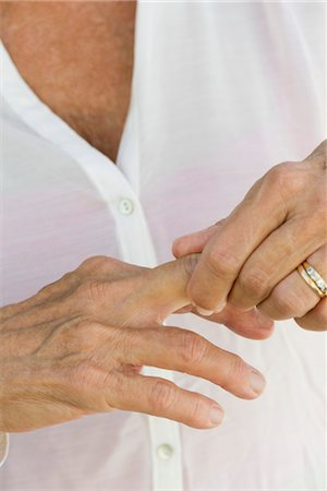 ring hand woman - Senior woman rubbing knuckles, cropped Stock Photo - Premium Royalty-Free, Code: 632-05816917