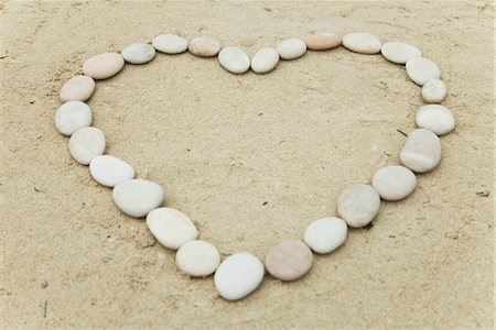 Pebbles arranged in heart shape on sand Stock Photo - Premium Royalty-Free, Code: 632-05816943