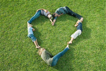 People lying on grass positioned in shape of heart Stock Photo - Premium Royalty-Free, Code: 632-05817001