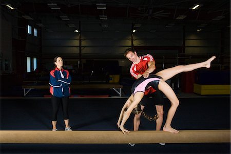 Female gymnast practicing on balance beam with coach Stock Photo - Premium Royalty-Free, Code: 632-05817017