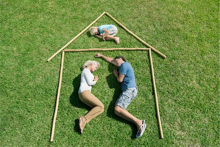 stick - Family with one child lying on grass within outline of house, high angle view Stock Photo - Premium Royalty-Free, Code: 632-05817110