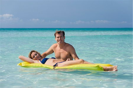 Couple relaxing in ocean, woman lying on pool raft, portrait Stock Photo - Premium Royalty-Free, Code: 632-05845044