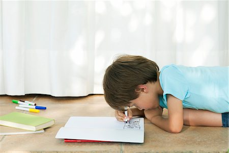 Boy drawing in notebook Stock Photo - Premium Royalty-Free, Code: 632-05845061