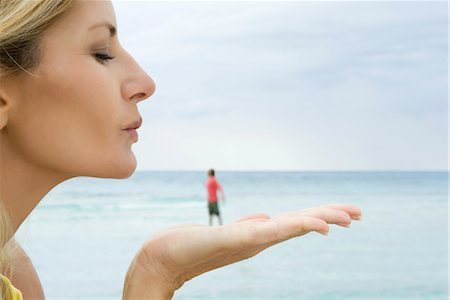 Woman appearing to blow a kiss at tiny man standing on her hand Stock Photo - Premium Royalty-Free, Code: 632-05845157