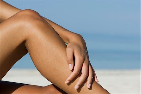 Woman touching bare legs at the beach, cropped Stock Photo - Premium Royalty-Free, Code: 632-05845152