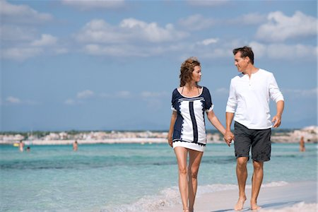 Couple walking on beach holding hands, portrait Stock Photo - Premium Royalty-Free, Code: 632-05845202