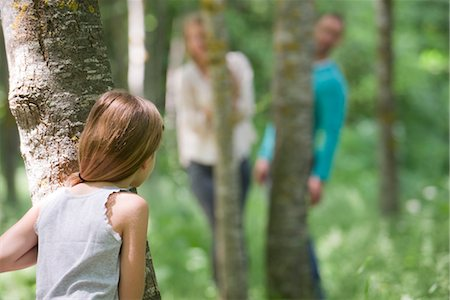 Girl playing hide and seek with parents in woods, rear view Stock Photo - Premium Royalty-Free, Code: 632-05845385