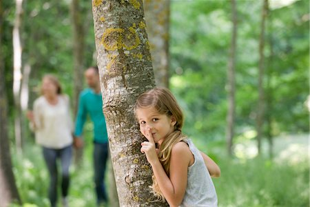 Girl hiding behind tree with finger on lips Stock Photo - Premium Royalty-Free, Code: 632-05845584