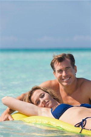 Couple relaxing in ocean, woman lying on pool raft, portrait Stock Photo - Premium Royalty-Free, Code: 632-05845600