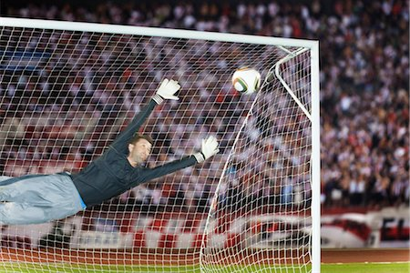 Soccer goalkeeper diving to block ball Stock Photo - Premium Royalty-Free, Code: 632-05991202