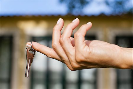 finger holding a key - Woman's hand holding key, cropped Stock Photo - Premium Royalty-Free, Code: 632-05991350