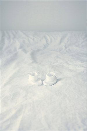 Baby booties on bed Stock Photo - Premium Royalty-Free, Code: 632-05991390