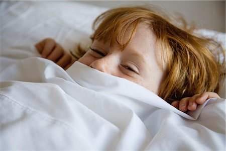 Boy lying in bed with bed sheet covering face Stock Photo - Premium Royalty-Free, Code: 632-05991729