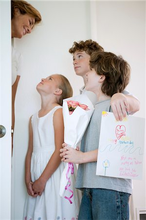 Children giving mother flowers and hand-made greeting card Stock Photo - Premium Royalty-Free, Code: 632-05991960