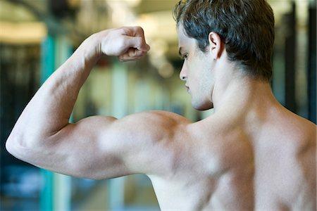 shirtless men - Young man flexing bicep muscles Stock Photo - Premium Royalty-Free, Code: 632-05992015