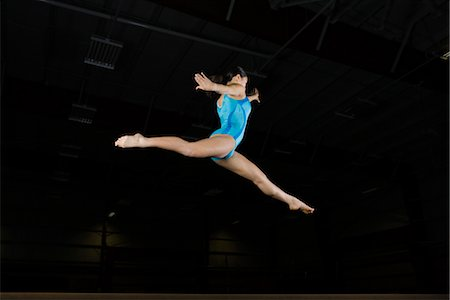Teenage girl gymnast performing split leap, low angle view Stock Photo - Premium Royalty-Free, Code: 632-05992264