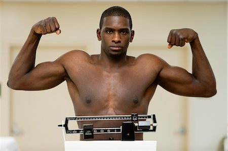 Young man flexing muscle on weight scale, portrait Stock Photo - Premium Royalty-Free, Code: 632-05992285