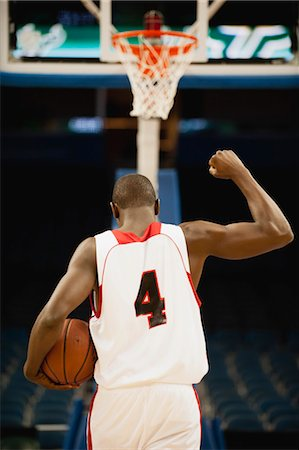 Basketball with fist raised in victory, rear view Stock Photo - Premium Royalty-Free, Code: 632-05992281