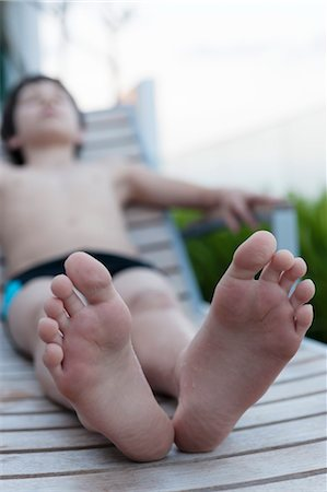 Boy reclining on deckchair, focus on bare feet Stock Photo - Premium Royalty-Free, Code: 632-06029285