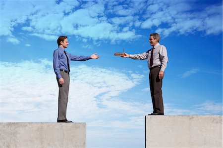 platform - Businessmen standing on platforms, one handing the other a tiny factory Stock Photo - Premium Royalty-Free, Code: 632-06029333