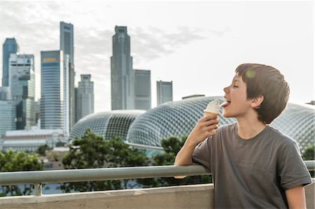 Boy eating ice cream cone, city skyline in background Stock Photo - Premium Royalty-Free, Code: 632-06029449