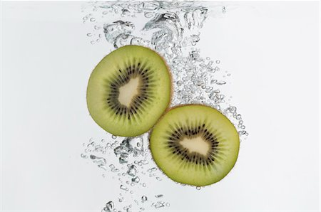 Kiwi halves submerged in water Stock Photo - Premium Royalty-Free, Code: 632-06029440
