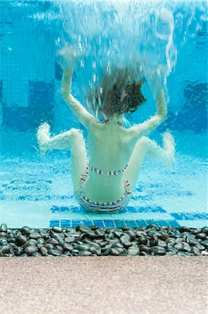 preteen girl swimsuit - Girl swimming underwater in swimming pool, rear view Stock Photo - Premium Royalty-Free, Code: 632-06029548