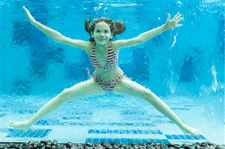 Girl swimming underwater in swimming pool Stock Photo - Premium Royalty-Free, Code: 632-06029540