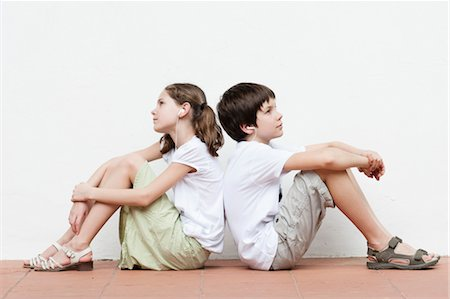 Boy and girl sitting back to back listening to music together Stock Photo - Premium Royalty-Free, Code: 632-06029670
