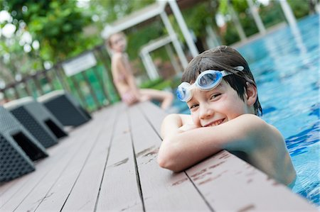 Boy with goggles leaning on edge of swimming pool, smiling Stock Photo - Premium Royalty-Free, Code: 632-06029834