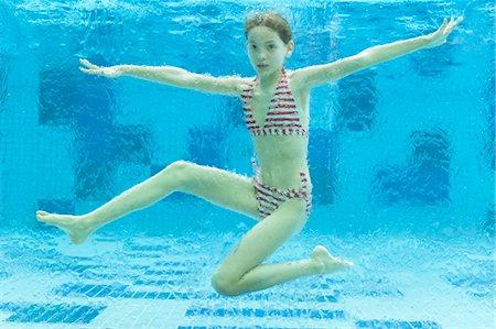 Girl swimming underwater in swimming pool Stock Photo - Premium Royalty-Free, Code: 632-06029838
