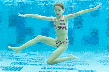 Girl swimming underwater in swimming pool Stock Photo - Premium Royalty-Free, Code: 632-06029838