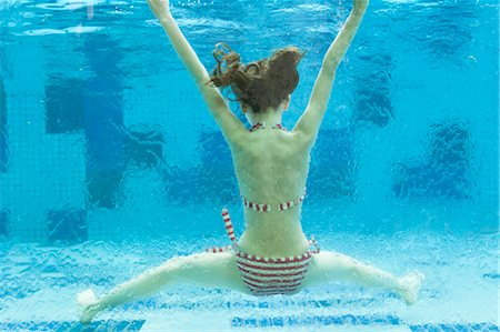 Girl swimming underwater in swimming pool, rear view Stock Photo - Premium Royalty-Free, Code: 632-06030001