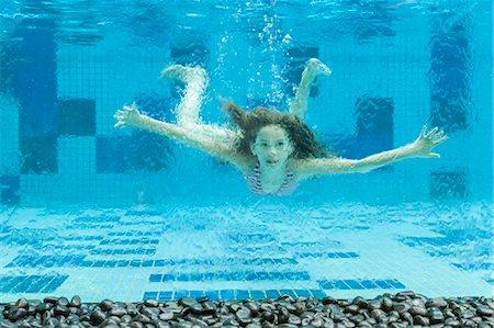 Girl swimming underwater in swimming pool Stock Photo - Premium Royalty-Free, Code: 632-06030040