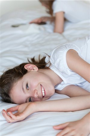 Girl lying on bed, smiling Stock Photo - Premium Royalty-Free, Code: 632-06030071