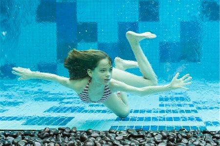 preteen bikini - Girl swimming underwater in swimming pool Stock Photo - Premium Royalty-Free, Code: 632-06030111