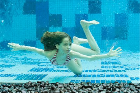 Girl swimming underwater in swimming pool Stock Photo - Premium Royalty-Free, Code: 632-06030111