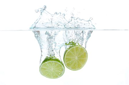 Lime halves splashing into water Stock Photo - Premium Royalty-Free, Code: 632-06030262