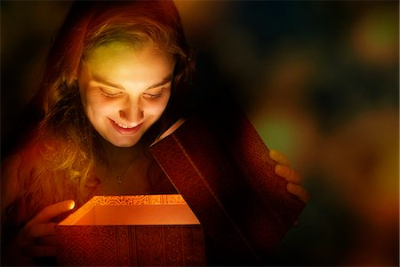 Young woman illuminated by golden light as she opens Christmas present Stock Photo - Premium Royalty-Free, Code: 632-06118157