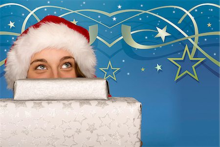 Young woman peeking over stack of Christmas gifts Stock Photo - Premium Royalty-Free, Code: 632-06118233