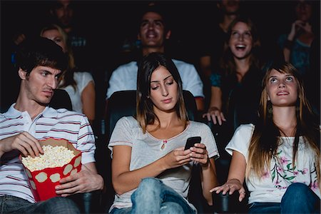 front row seat - Woman using cell phone in movie theater, man looking over with annoyed expression Stock Photo - Premium Royalty-Free, Code: 632-06118278
