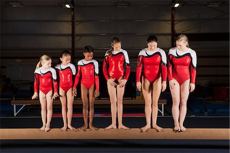 Female gymnasts of various ages standing in a row on balance beam Stock Photo - Premium Royalty-Free, Code: 632-06118279