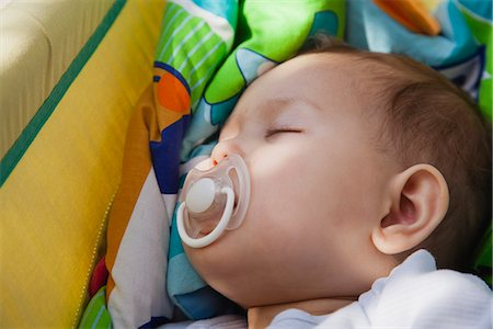 sucking - Baby girl napping with pacifier in her mouth Stock Photo - Premium Royalty-Free, Code: 632-06118293