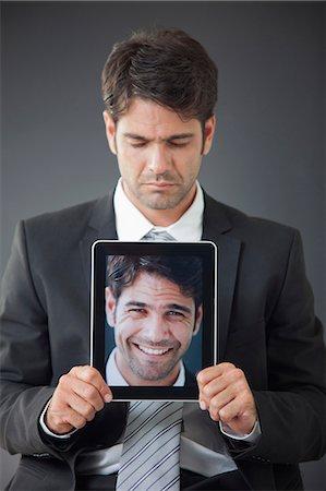 dece11 - Man holding up digital tablet displaying image of himself smiling Stock Photo - Premium Royalty-Free, Code: 632-06118321