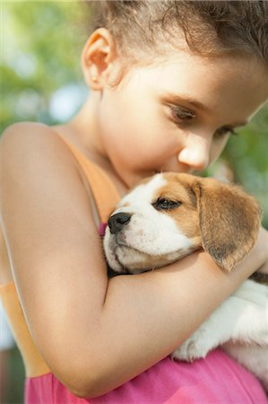 dog kissing girl - Girl kissing beagle puppy Stock Photo - Premium Royalty-Free, Code: 632-06118340