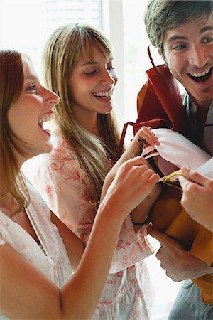 Women grabbing gift bags in man's arms Stock Photo - Premium Royalty-Free, Code: 632-06118420