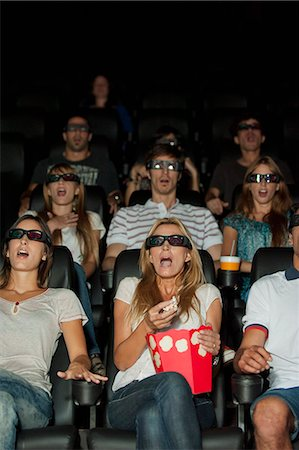 front row seat - Audience wearing 3-D glasses in movie theater with shocked expressions on faces Stock Photo - Premium Royalty-Free, Code: 632-06118470