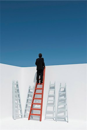 Businessman climbing ladder, rear view Stock Photo - Premium Royalty-Free, Code: 632-06118473