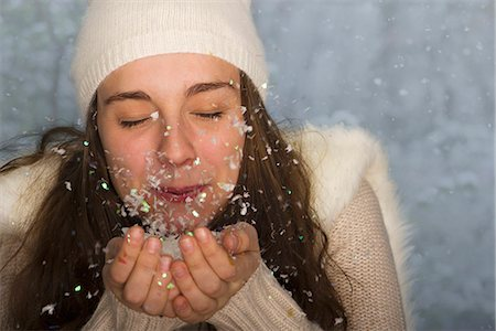 Young woman wearing winter clothing, blowing handful of confetti Stock Photo - Premium Royalty-Free, Code: 632-06118488